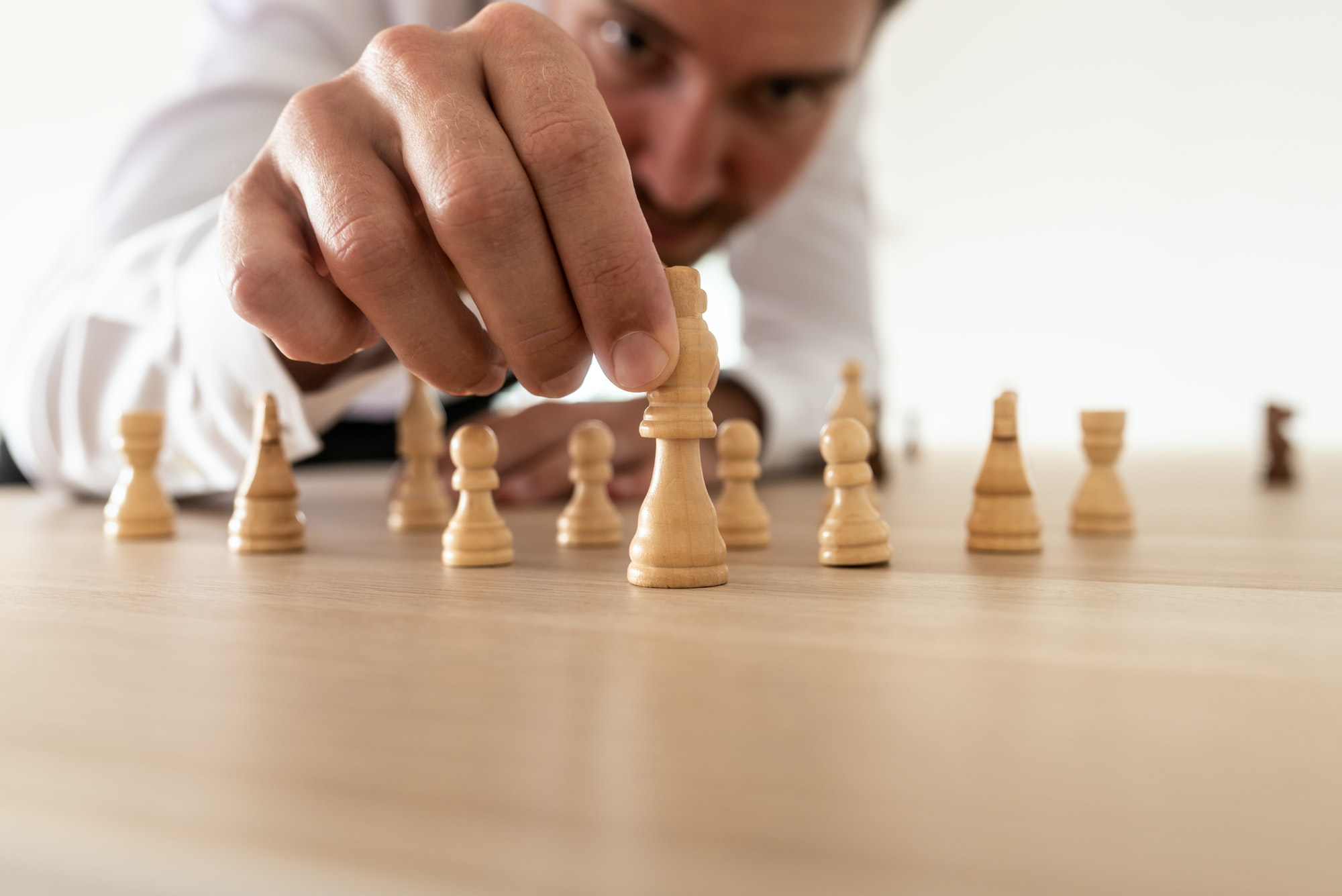 Business leader arranging chess pieces with king in the leading position