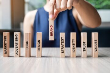 Businesswoman hand placing wooden Dominoes with text