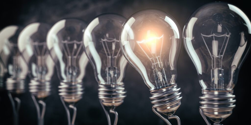 Row of light bulb with a one glowing. Idea and innovation concept.